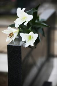 White lilies on black granite tombstone outdoors